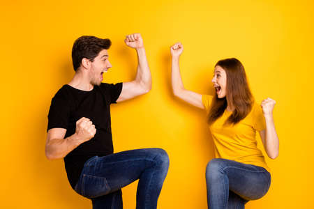 Photo of crazy rejoicing boyfriend and girlfriend overjoyed about sales and discounts where they bought jeans denim black t-shirt isolated over vivid yellow color background