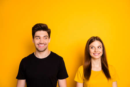 Photo of cheerful positive toothy beaming cute couple of two people wearing black t-shirt smiling at each other taking the hint isolated over vivid color background