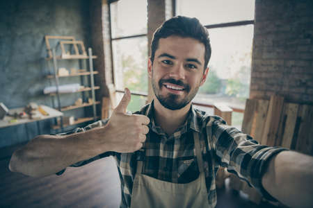 Closeup photo of handsome guy master raising thumb up making selfies in new own wooden business industry studio looking customers woodwork shop garage indoors Standard-Bild