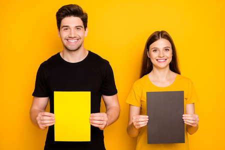 Photo of cheerful cute nice couple of two spouses presenting you two pieces of paper held with hands with empty space on them isolated over vibrant shiny bright color background in black t-shirt