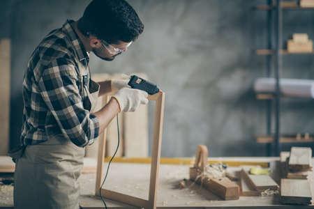 Profielfoto aan de zijkant van een serieuze geconcentreerde werker die een elektrisch heet lijmpistool gebruikt om houten constructieframes in de garage van het huis te repareren