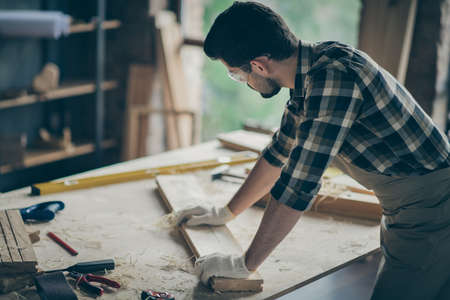 Back rear side view photo of concentrated man workman work with wooden long plane restored furniture check smoothing in home garage