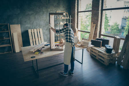 Back rear side full length photo of concentrated worker handcraft entrepreneur renew slab table use drill fix woodwork in home house garage