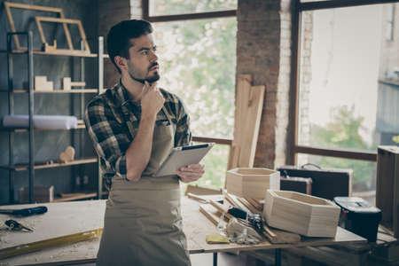 Nachdenklicher Hartholz-Vorarbeiter, professioneller Arbeiter, der Tablette verwendet, denkt, entscheiden Sie sich für die Auswahl der Kunden für die Reparatur von Restaurierungsaufträgen in der Hausgarage