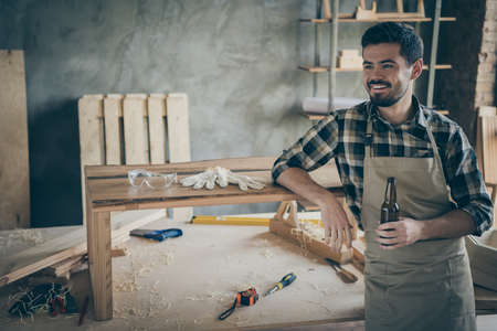 Profile side photo of positive cheerful worker hardwood worker complete his renovation slab table order relax rest hold bottle beer enjoy in house home garage