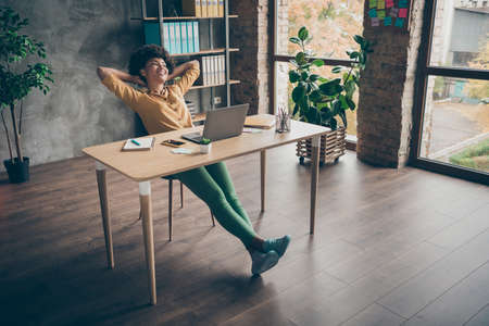Full length photo of peaceful afro american girl complete her startup work presentation sit table stretch hands dreamy weekends wear casual style clothing in loft workplace office