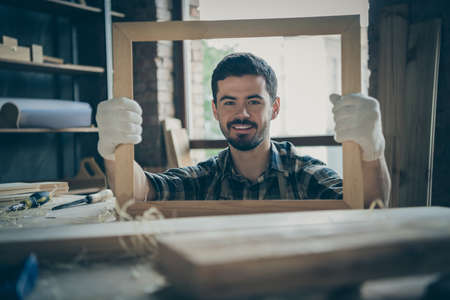 Photo of cheerful cute man having finished making frame holding it looking through wooden handmade smiling toothily at you Standard-Bild