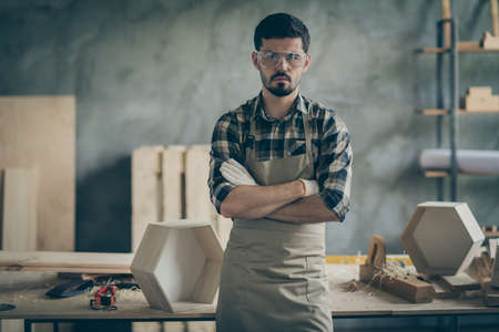 Masculine confident workman builder stand in house home garage cross hands ready repair restor all furniture workshop wear checkered plaid shirt Stockfoto