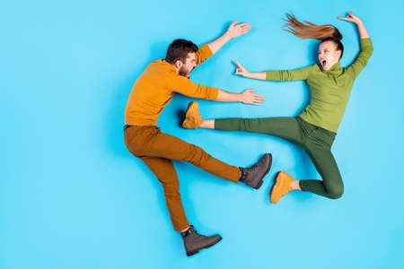 Side profile full length body size top above high angle view photo of crazy mad insane couple of karatists girl kicking man away with leg casually screaming rageously isolated pastel blue color background Stock Photo