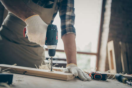 Cropped clsoe up photo of man drilling wood equipped with gloves doing his work indoors using modern instruments