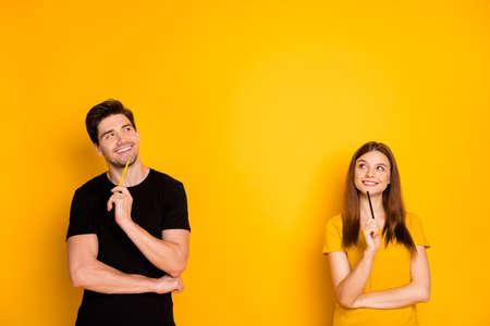 Foto de alegre positivo lindo agradable pareja bonita encantadora sosteniendo bolígrafos con camiseta negra sonriendo con dientes mirando hacia el espacio vacío un ataque de pensamientos aislados sobre fondo de color brillante brillante