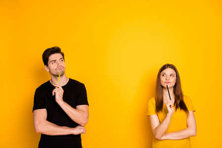 Photo of thoughtful guessing thinking couple of two people pondering over their new project being worked on by them as freelancers isolated over vivid color background in black t-shirt