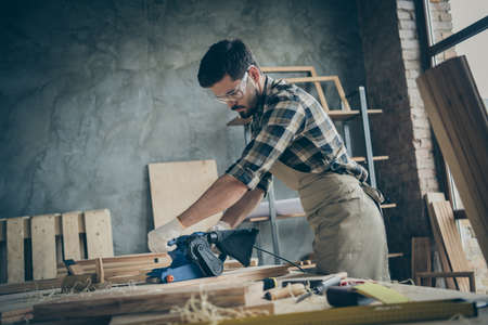 Side profile photo of serious pensive confident man processing wood with sander machine with eyes protected eye wear in checkered shirt gloves Banque d'images - 134708111