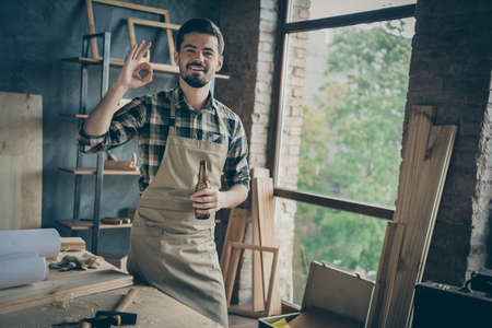 Photo of cheerful bearded positive man showing, ok sign in apron checkered shirt holding bottle of beer having finished woodwork