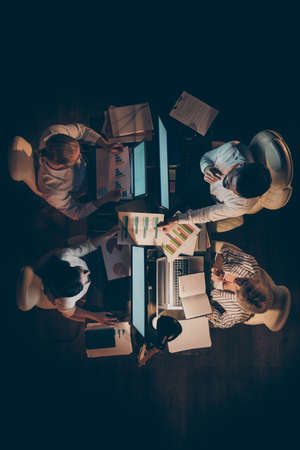 High angle above view vertical photo of hard-working four business people working overtime night looking charts schemes brainstorming lamp light dark office indoors