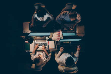 High angle above view photo of four busy partners business men women working overtime looking computer screen typing corporate email lamp light dark office indoors Stok Fotoğraf