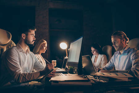 Profile side view of four people sitting in front of screen writing code solving tech issue supporting clients analyzing IT documents task deadline at late night work place station