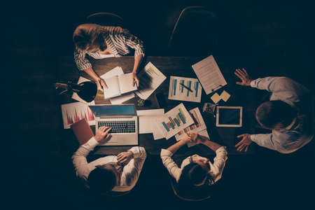 Top above high angle view of smart clever hardworking business people top executive managers working with data preparing report presentation at late night workplace workstation Stock Photo