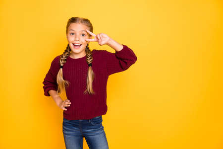 Portrait of her she nice attractive, lovely charming girlish cheerful cheery pre-teen girl showing v-sign near eye having fun isolated on bright vivid shine vibrant yellow color background