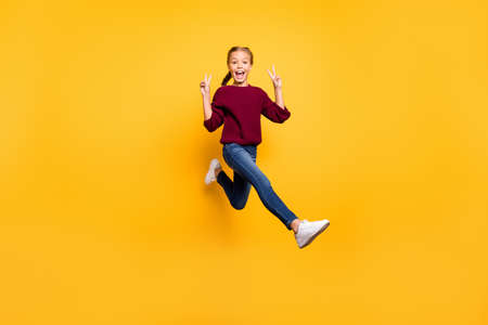 Full length body size view of her she nice attractive cheerful cheery, playful pre-teen girl having fun jumping showing double v-sign isolated on bright vivid shine vibrant yellow color background
