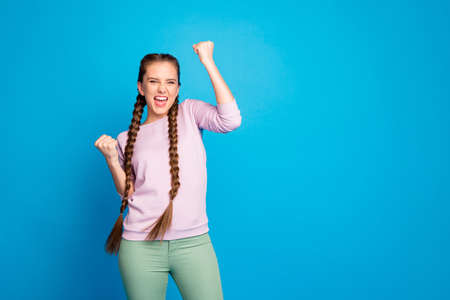 Photo of pretty lady long braids raising fists celebrating favorite football, team goal winning match wear casual pullover trousers isolated blue color background
