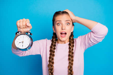 Close up photo of anxious worried youth girl with braids pigtails oversleep, hold clock find she late feel frustrated expression shout omg wear casual style clothing isolated blue color background