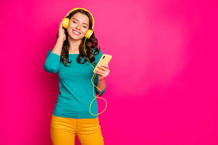 Photo of white cheerful positive nice pretty cute girlfriend smiling toothily, listening to music enjoying free time isolated pink bright color background