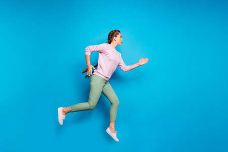 Full length profile photo of pretty lady long braids jumping high sports, competition run to finish line wear casual pink pullover green pants isolated blue color background