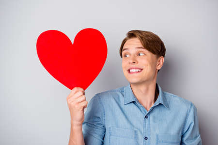 Portrait of cheerful candid guy feel shy cant give big red paper card heart his dream girl girlfriend look wear stylish clothing isolated over, grey color background
