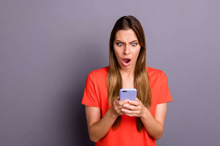 Omg unbelievable. Impressed frustrated girl use her smartphone read social network, news got notification scream wear beautiful clothes isolated over grey color background