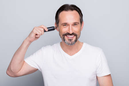 Photo of handsome aged man guy metrosexual hold electric trimmer painless procedure delete nose hair started trimming ears wear white t-shirt isolated grey color background