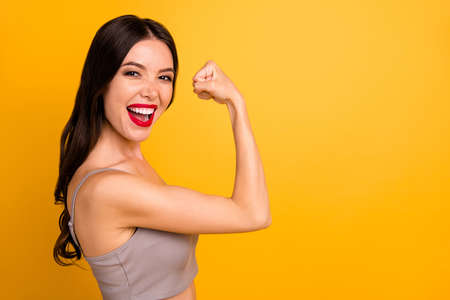 Side profile close up photo of cheerful strong powerful woman demonstrating her triceps elbow near empty space with lips pomaded isolated vivid color background Stock Photo