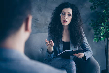 Portrait of her she nice attractive skilled wavy-haired girl psychologist shark expert sitting in chair listening talking to client assistance gray concrete wall background workplace workstation