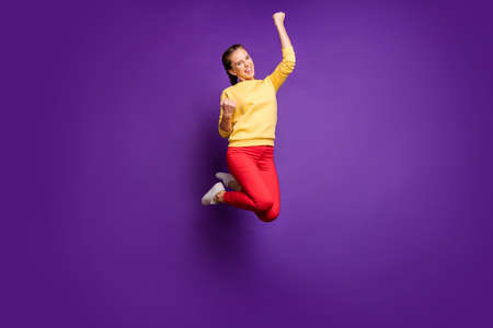 Goal. Full length photo of teen lady jumping high celebrating best win of football team wear casual yellow pullover red pants isolated purple color background