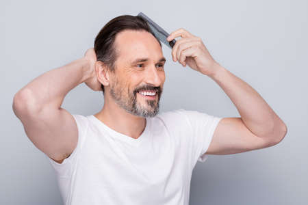 Closeup photo of macho cheerful mature guy holding new hairbrush try quality of product on himself feel good result on hairstyle wear white t-shirt isolated grey color background