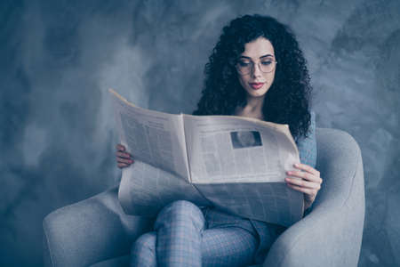 Portrait of her she nice-looking attractive lovely cute charming calm focused peaceful wavy-haired girl sitting in chair reading digest news magazine isolated over gray concrete wall background