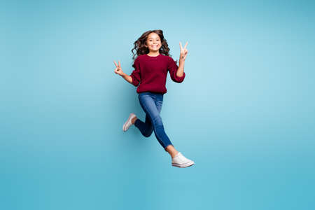 Full length body size turned photo of cheerful funny funky positive girl wearing denim footwear burgundy sweater showing you v-sign double isolated vivid color background