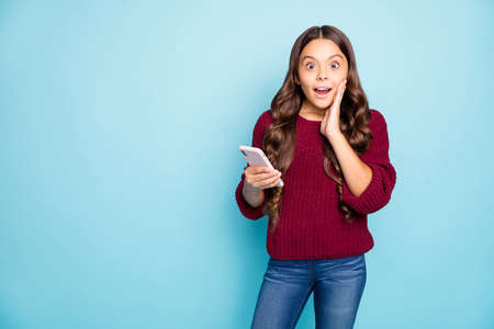 Photo of cheerful positive funky funny schoolchild in jeans denim burgundy sweater expressing amazement on face holding telephone isolated vibrant color blue background