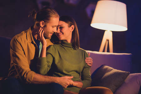 Close-up portrait of his he her she nice attractive lovely affectionate tender lovable cheerful dreamy couple girl sitting on divan spending day weekend kissing at night dark home house apartment Reklamní fotografie