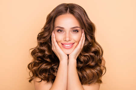Close-up portrait of her she nice-looking attractive sweet tender feminine cheerful cheery wavy-haired girl touching cheeks enjoying isolated over beige pastel color background Banco de Imagens