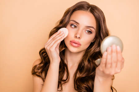 Close up photo of focused dreamy girl look at mirror apply powder with cotton pad prepare for date isolated over beige color background Archivio Fotografico - 135268546