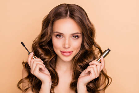 Close up photo of charming attractive lady hold mascara want prepare for date isolated over beige color background Archivio Fotografico - 135268548