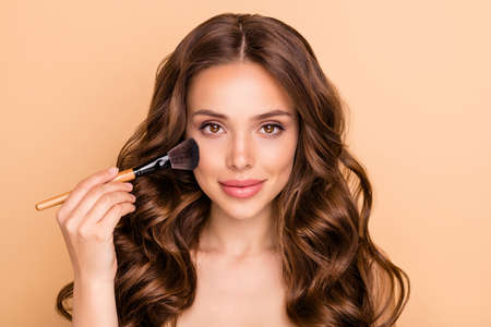 Close up photo of gorgeous glamorous wavy haired girl apply rouge powder hold brush want prepare for date be attractive use professional skin care products isolated over beige color background Archivio Fotografico - 135268561