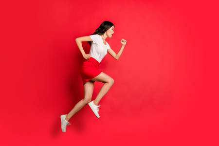 Full length body size profile side view of nice attractive lovely purposeful focused slim fit thin wavy-haired girl jumping running fast isolated over bright vivid shine vibrant red color background