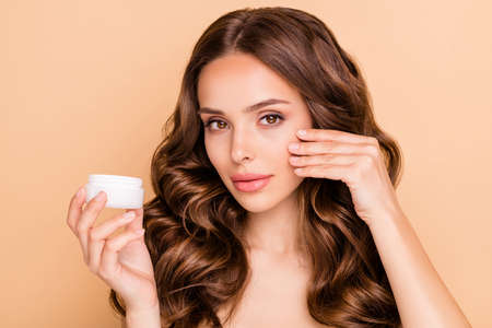 Daily skin care hygiene. Close up photo of dreamy focused girl apply cream want make her skin pure perfect smooth isolated over beige color background Archivio Fotografico - 135268616