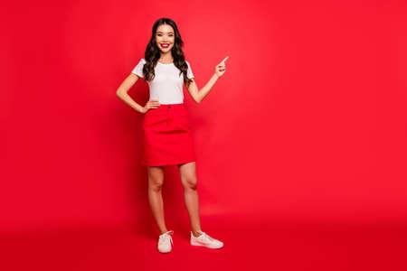 Vista de longitud completa del tamaño del cuerpo de ella ella agradable atractiva bastante encantadora alegre alegre alegre chica de pelo ondulado señalando el espacio de copia de anuncio de anuncio aislado sobre fondo de color rojo vibrante de brillo vivo brillante