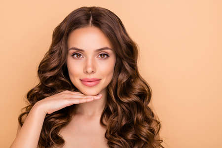 Close-up portrait of her she nice-looking attractive lovely sweet tender peaceful wavy-haired girl touching chin showing facelift effect isolated over beige pastel color background