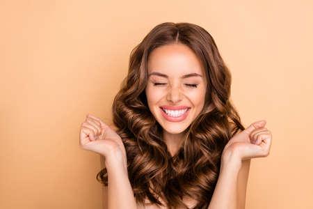 Close-up portret van mooie aantrekkelijke mooie prachtige meisjesachtige opgewonden vrolijke vrolijke dromerige gelukkige golvende haren meisje genieten van verwacht plezier geïsoleerd op beige pastel kleur achtergrond