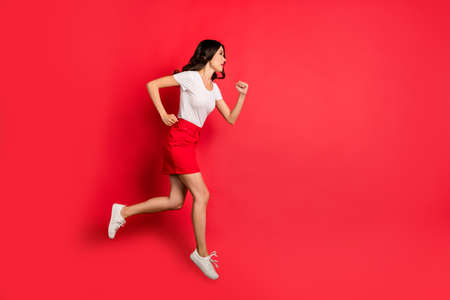 Full length body size profile side view of her she nice attractive lovely pretty serious slim fit wavy-haired girl jumping running fast isolated over bright vivid shine vibrant red color background