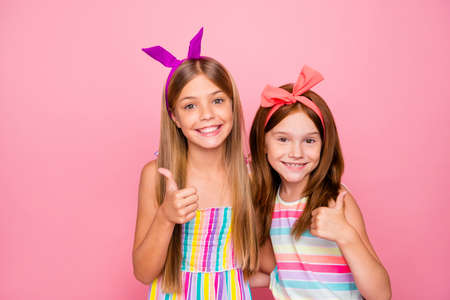 Close up photo of charming kids hugging embracing showing thumb up wearing bright headbands skirt dress isolated over pink background Reklamní fotografie